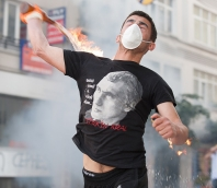 A young man wearing a surgical mask over his mouth hurls a Molotov cocktail.