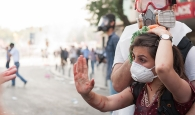 In the midst of tear gas, a woman wearing a surgical mask  holds up a hand to refuse assistance being offered by another hand. Blood drips down her neck and her arms.
