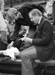 Neil Armstrong, wearing a suit, sits on a bleacher to create a paper airplane.