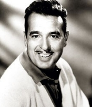 An old black and white photo of Tennessee Ernie Ford wearing a cardigan sweataer.