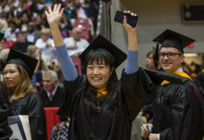 A UC student raised and waved her arms as her family cheers for her during the Doctoral Hooding & Master's Recognition Ceremony Friday May 1, 2015 at Fifth Third Arena. UC/Joseph Fuqua II
