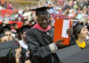 Samuel Ochiel Obura stands with his dissertation as he got recognized by President Santa Ono Friday May 1, 2015 at Fifth Third Arena. Samuel Ochiel Obura from Kenya, returns after 50 years to take part in his Political Science, master's/hooding ceremony and receive a specially bound copy of his dissertation at Fifth Third Arena. UC/Joseph Fuqua II