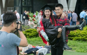 Female student carried with flowers as she posed for photos outside of Fifth Third Arena. UC/Andrew Higley