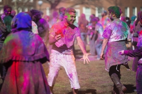 UC students throw colored powder on McMicken Commons as part of Holi Festival.