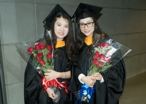 UC graduates pose with flowers after the Doctoral Hooding and Master's Recognition Ceremony