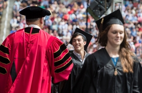 Grads walk across stage at Nippert Stadium