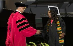 UC President Neville Pinto shakes hands with a graduating student.