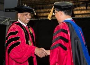 UC President Neville Pinto shakes a graduate's hand.