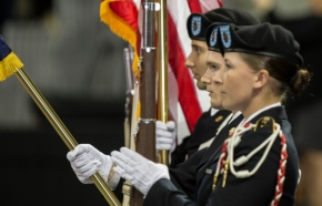 Soldiers serving as color guard stand at attention during the National Anthem.