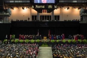 A wide shot of the stage at BB&T Arena with faculty and graduates seated.