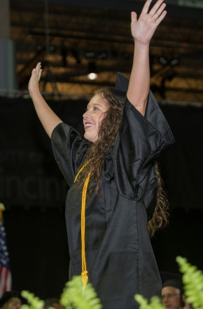 A student raises her arms victoriously on the stage.