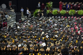 Wide shot of graduates sitting down facing stage.