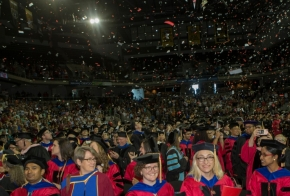 A wide shot of graduates and their family and friends in the audience.