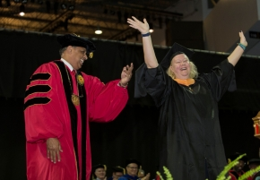 UC President Neville Pinto looks on as a student raises her arms on the stage.
