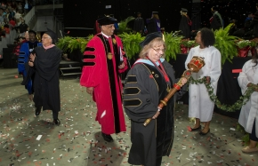 UC faculty and leadership make their entrance at commencement, led by a woman carrying a scepter.