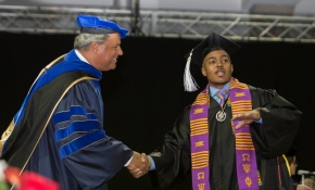 College of Arts and Sciences Dean Ken Petren shakes a student's hand.