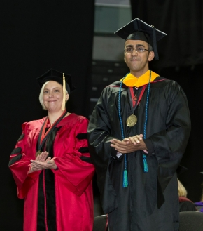 Two UC students stand to be recognized at Commencement.