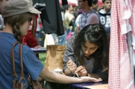 A student gets a henna tattoo.