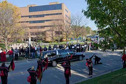 The UC Band stands at attention as the hearse passes.