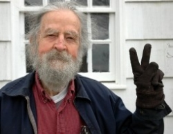 Gordon Maham, gray-haired and bearded, gives a peace sign.