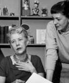 Ruth Lyons sitting at a desk, with Elsa standing my her side.