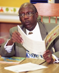 Lionel Brown sits at a table reading a book to students. The long-time education died in May 2014.