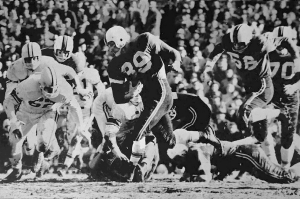 A football running back for the University of Cincinnati runs through the opposing team.