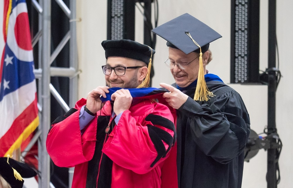 A doctoral candidate receives his hood.