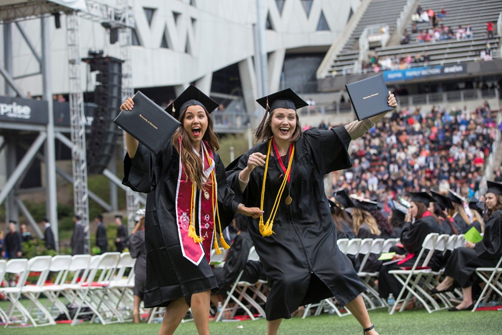 Two female students show off their diplomas.
