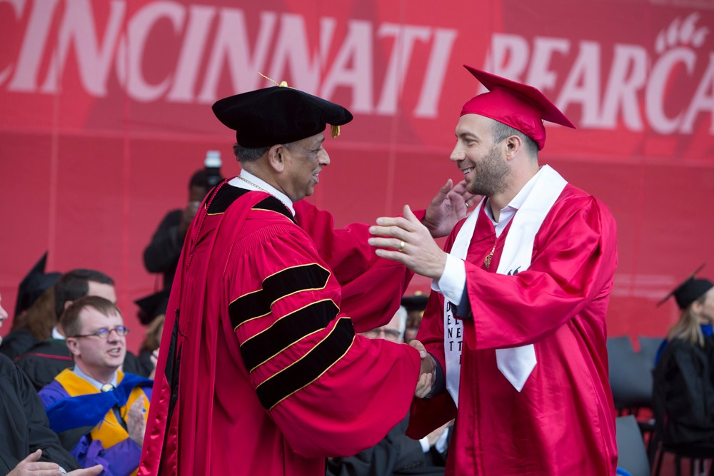 A male student gives the thumbs-up after receiving his diploma.