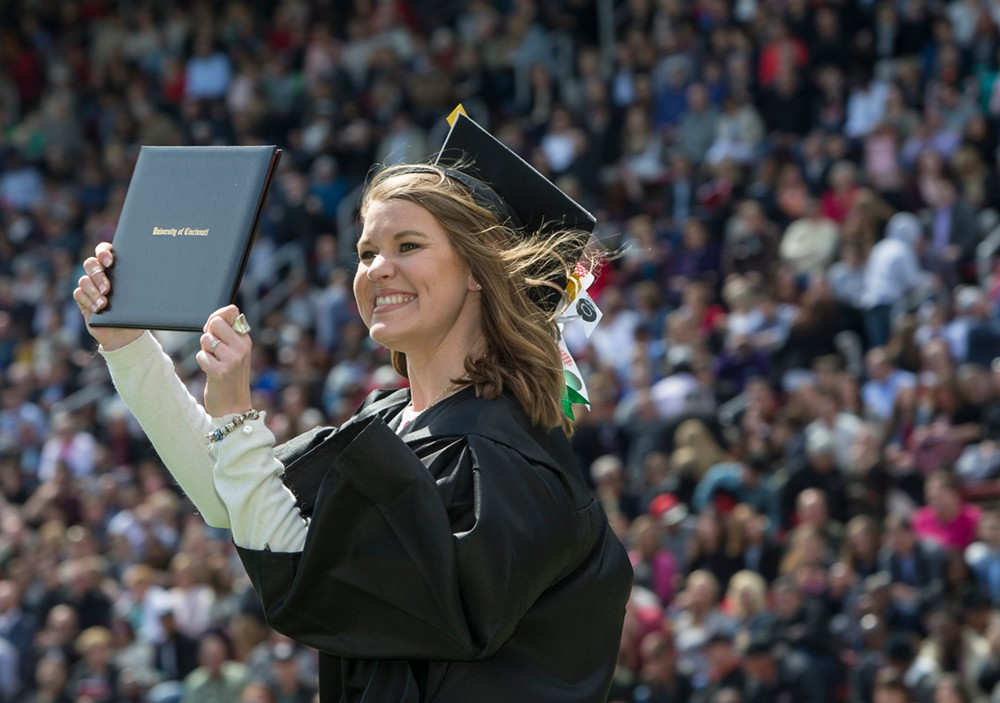 A student beams as she shows off her diploma.