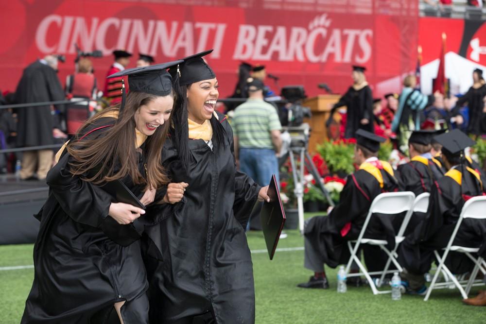 Two female grads share a laugh.