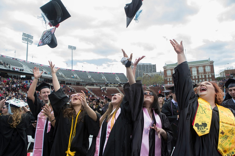 Students toss their mortarboards into the air.