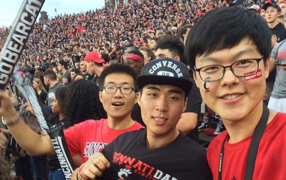UC students from China cheer the home team at Nippert Stadium.