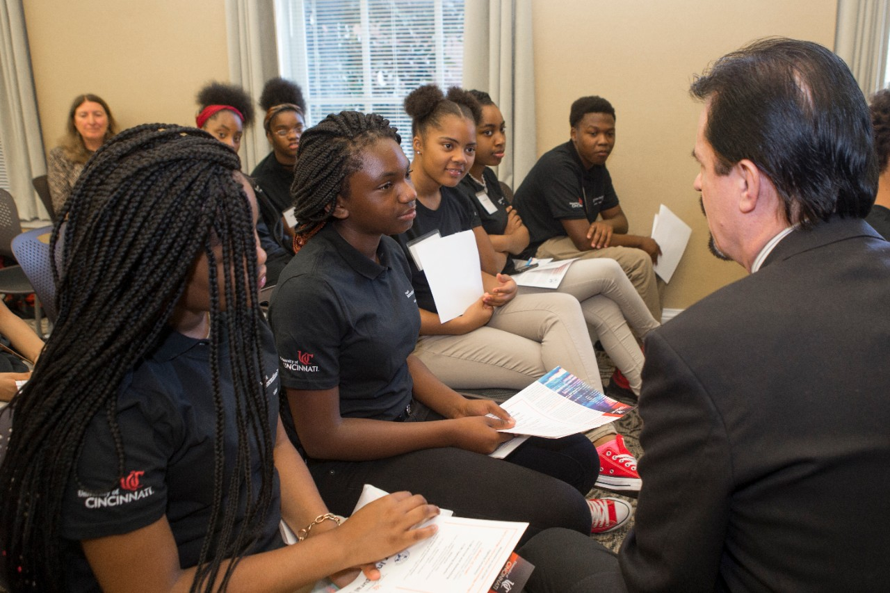 Several Hughes STEM High School ninth graders interact with an attendee at the signing ceremony.