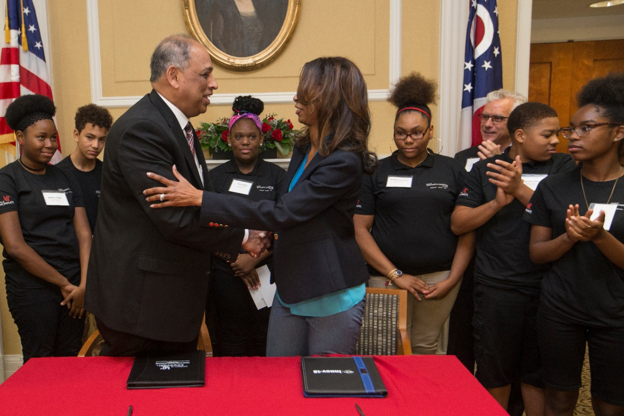 UC President Neville Pinto, left, and CPS Superintendent Laura Mitchell shake hands after signing the agreement formalizing the creation of the Early College Information Technology program.