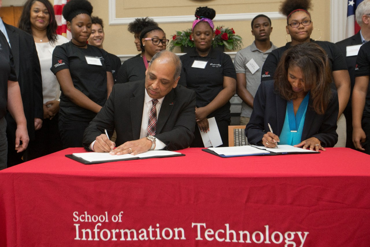 UC President Neville Pinto, left, and CPS Superintendent Laura Mitchell sign a bilateral agreement forming a new Early College Information Technology program.