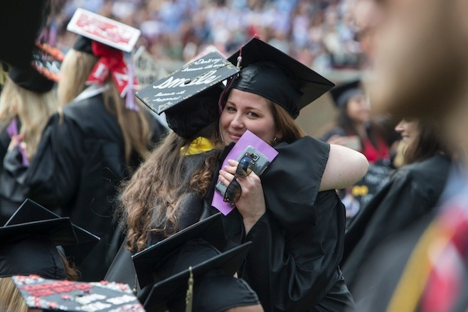 Students hug during Commencement