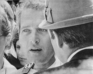 Paul Newman being interviewed by a reporter wearing a hat.