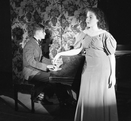 A student sings at the piano, played by another student.