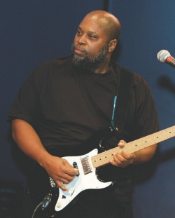 Raymond Towler plays a guitar in a band