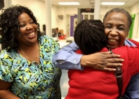 With a giant smile on his face, David Ayers hugs a family member while another one waits her turn.
