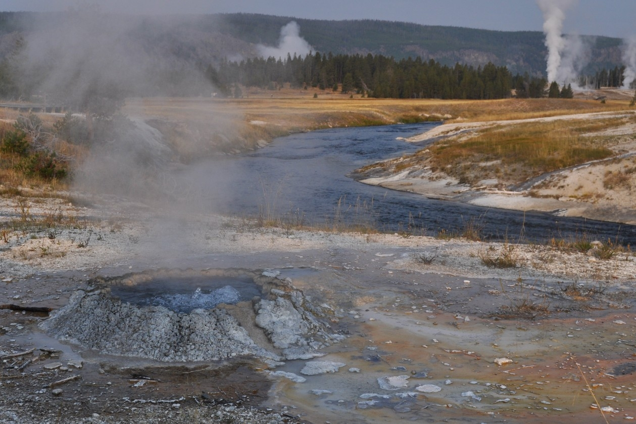 A team of geologists stands near one of Yellowstone's famed hot springs. The deep blue color comes from the scattered light of the sun passing through the clear water. (Photo by Annie Gangidine)