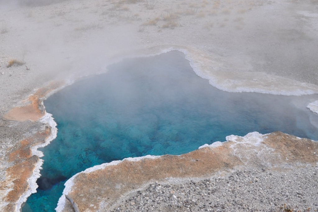 Geyser basins can be dangerous. Hot springs such as this one viewed from a park boardwalk form a thin crust over a boiling hydrothermal pool.