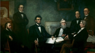 Lincoln is seated at a table with five other gentlemen, all in suits and ties, standing or sitting around him.