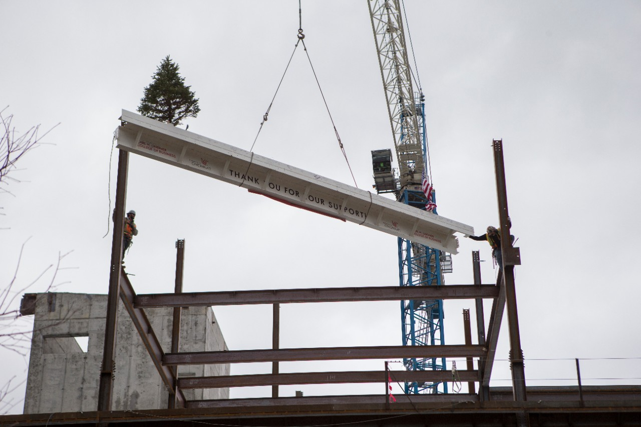 The crane guides the beam into position, where two construction workers wait to guide it