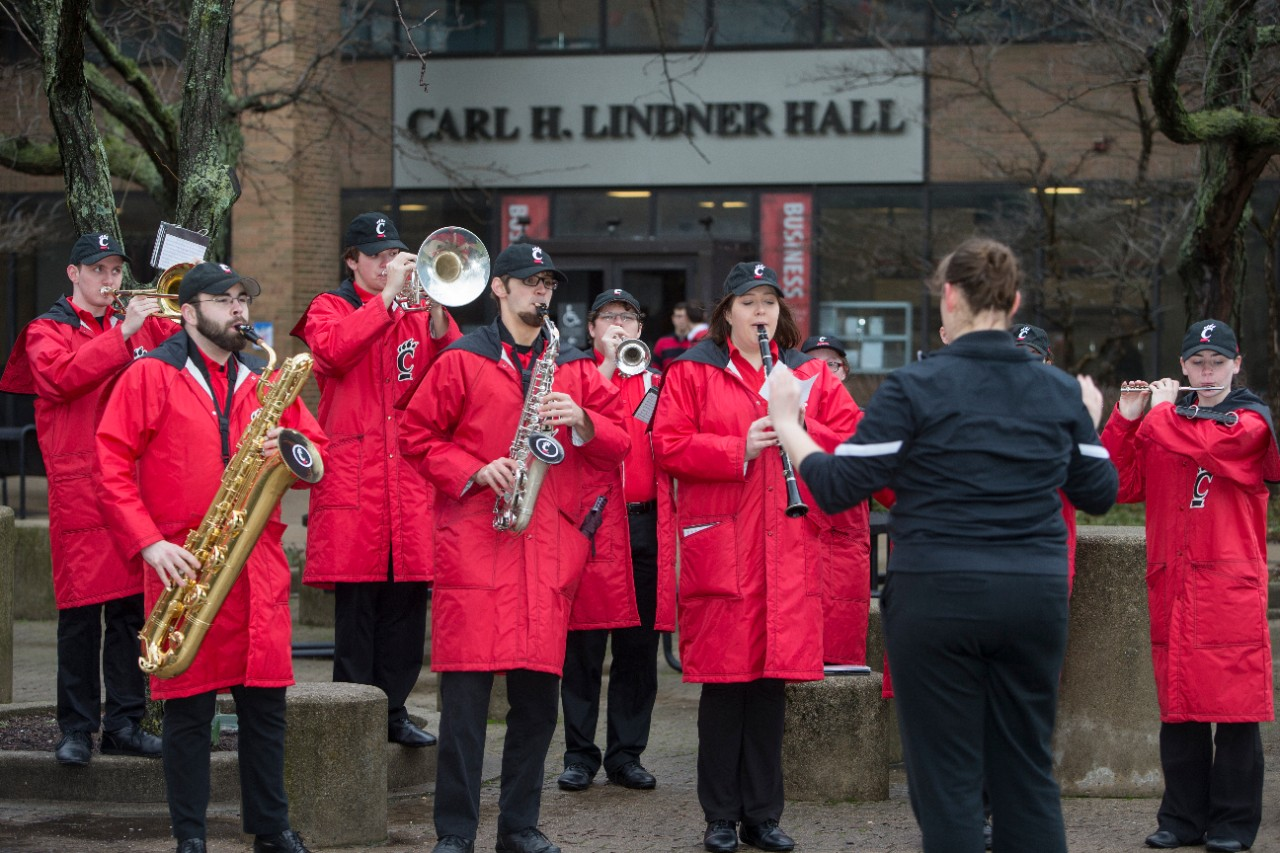 Members of the UC marching band play outside of Lindner Hall.