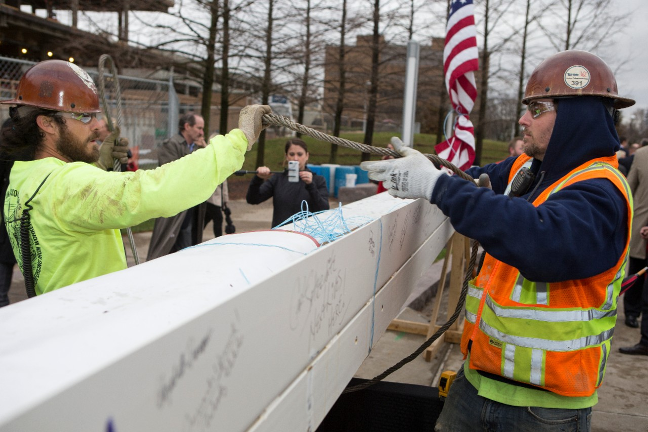 Construction workers prepare the beam to be hoisted into position.