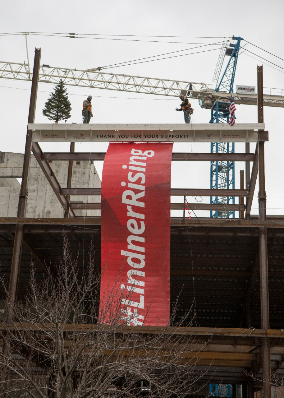 A banner that reads #Lindner Rising hangs from the final beam on the Lindner College of Business' new building.