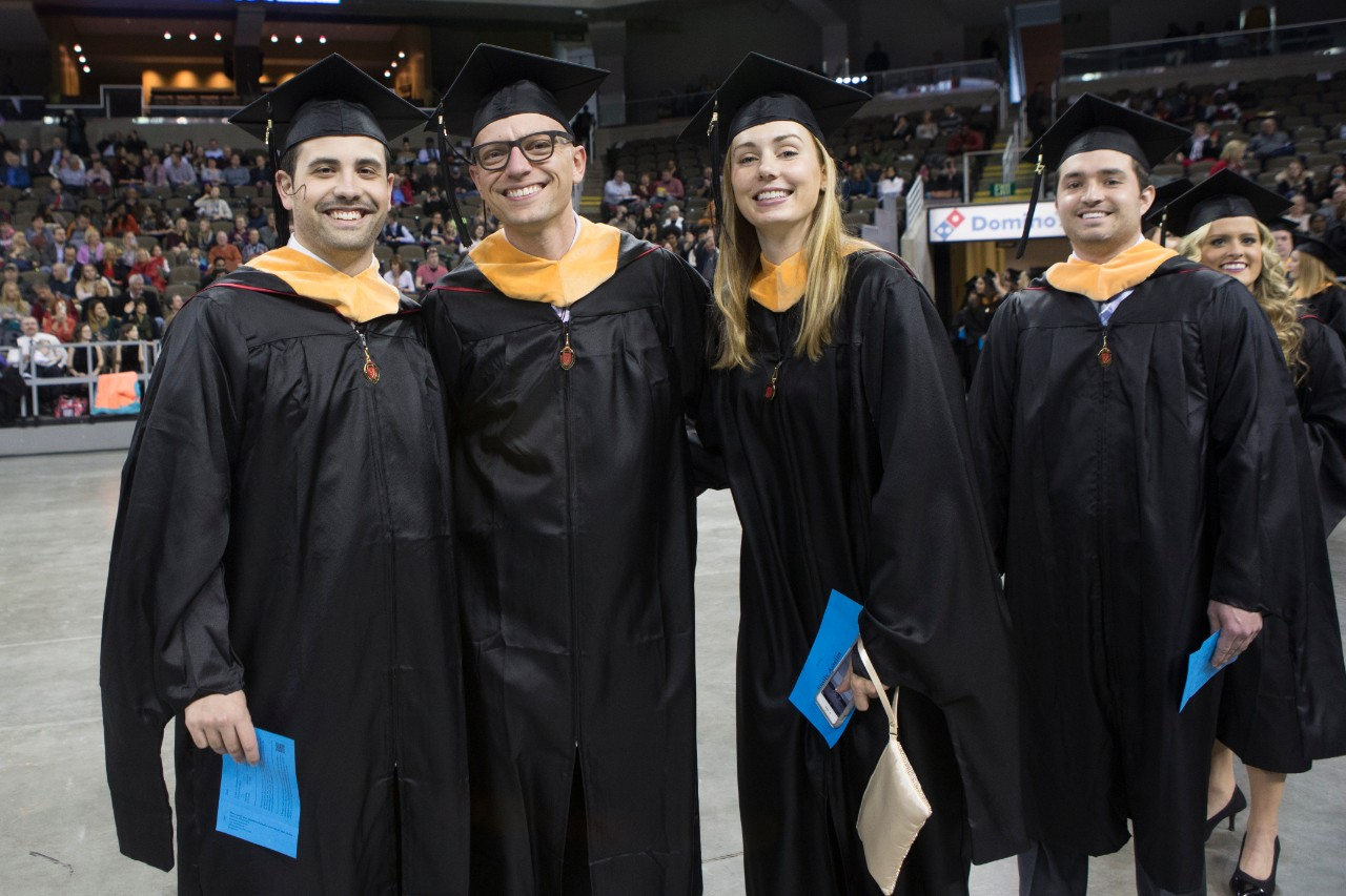 Four students smile at commencement.